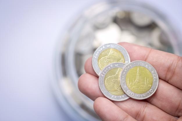 Trois pièces de monnaie sur dix en argent et bahts avec des pièces de bouteilles en verre Photo Premium