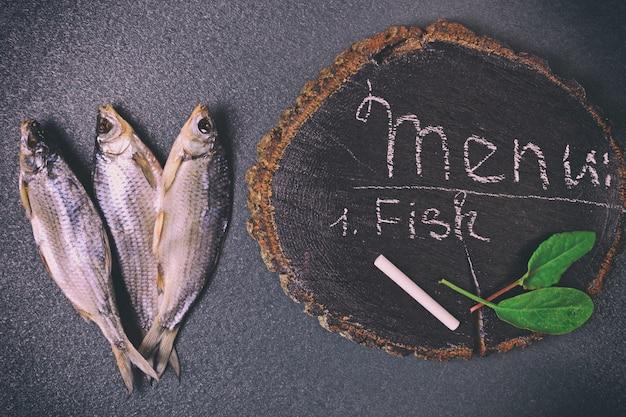 Trois poissons séchés sur une surface noire Photo Premium