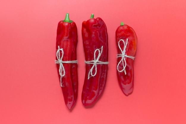 Trois Poivrons Rouges Avec Fil Rouge Sur Fond Rouge Photo Premium