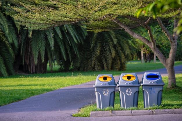 Trois Poubelles Dans Un Parc Avec Arbre Vert Et Plantes Dans Un Parc Public Photo Premium