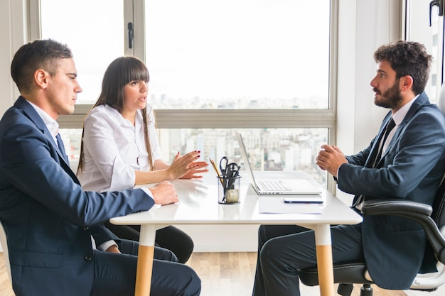 Trois professionnels discutant au bureau Photo gratuit