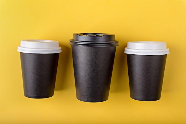 Trois Tasses En Papier Noir Jetables De Différentes Tailles Pour Le Café à Emporter à Plat Poser Sur Fond Jaune Photo Premium