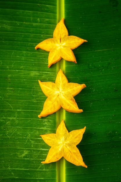 Trois tranches de carambole de fruit étoile jaune mûr ou pomme étoile (carambole) sur feuille de bananier vert, composition verticale Photo Premium