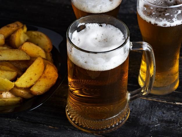 Trois verres de bière légère et pommes de terre de pays sur une table sombre Photo Premium