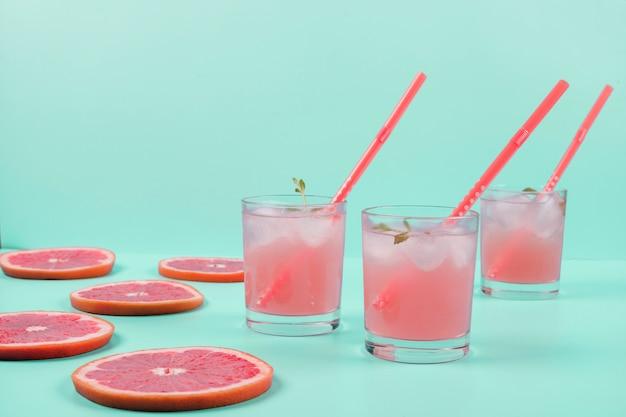 Trois verres de jus de pamplemousse froid et des tranches sur le fond de menthe Photo gratuit