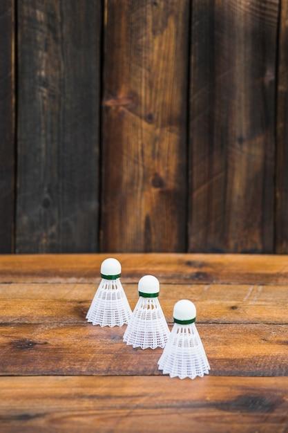 Trois volants blancs sur une table en bois Photo gratuit