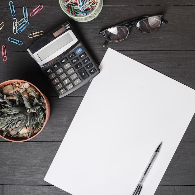 Trombones; calculatrice; lunettes; plante en pot avec un stylo sur du papier blanc vierge Photo gratuit