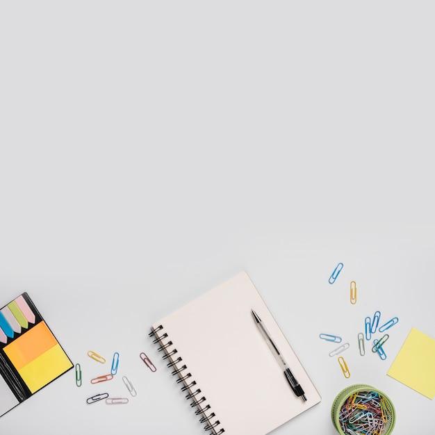 Trombones colorés; cahier à spirale avec stylo et notes autocollantes sur fond blanc Photo gratuit