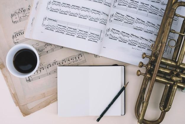 Trompette Et Partitions Près De Boisson Et Bloc-notes Photo gratuit