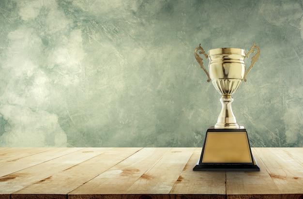 Trophée D'or Champion Placé Sur Une Table En Bois Avec Fond De Mur Vintage Photo Premium