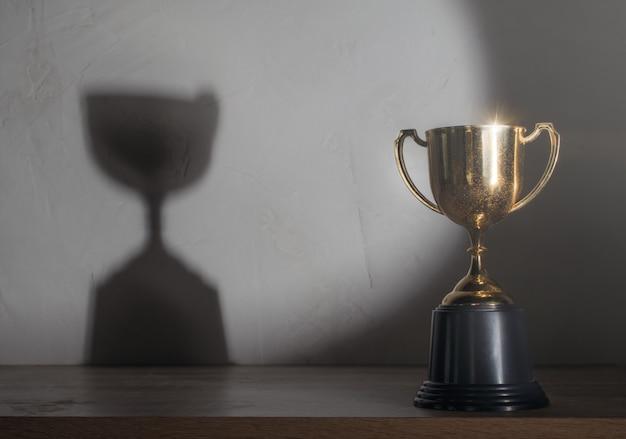 Trophée D'or Champion Placé Sur Une Table En Bois Photo Premium