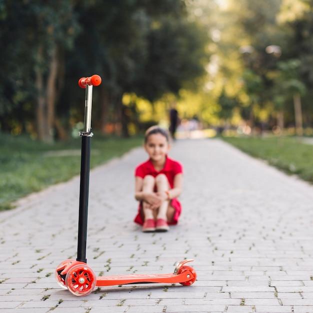 Trottinette rouge devant une fille assise sur une passerelle dans le parc Photo gratuit