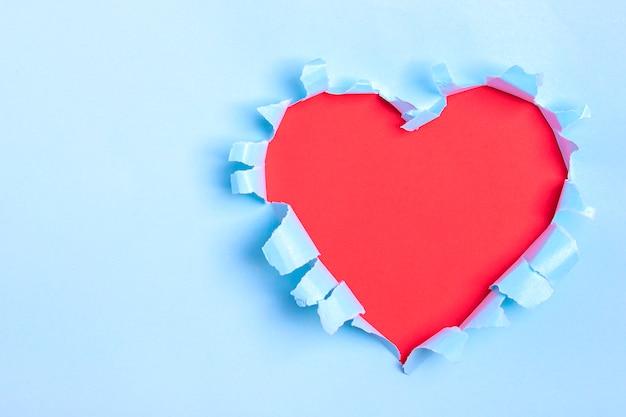 Trou en forme de coeur rouge à travers du papier bleu Photo Premium