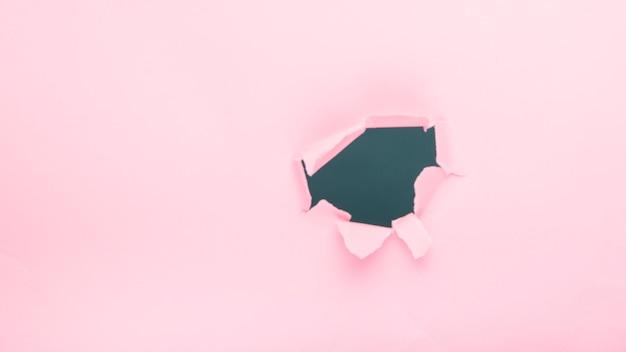 Trou sur papier rose Photo gratuit