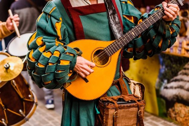 Troubadour médiéval jouant de la guitare antique. Photo Premium