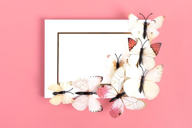 Troupeau de papillons sur cadre photo blanc sur fond rose Photo Premium