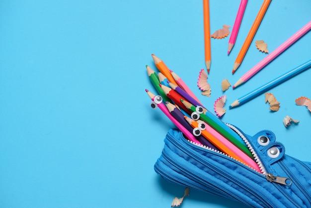 Trousse à crayons drôle mangeant des crayons sur bleu Photo Premium