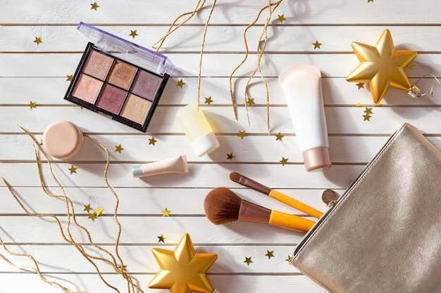 Trousse de maquillage avec maquillage, ombres à paupières, pinceaux pour le visage, crèmes et lotions à noël avec des étoiles dorées. Photo Premium