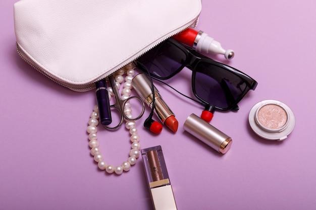 Trousse de maquillage avec des produits cosmétiques isolé sur fond rose Photo Premium