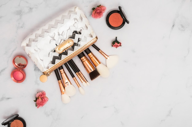 Trousse de maquillage professionnelle avec pinceaux et poudre compacte sur fond de marbre Photo gratuit