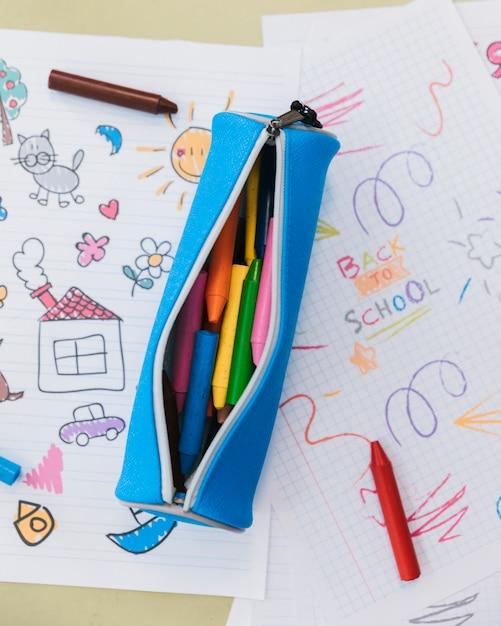 Trousse Ouverte Avec Des Crayons De Cire Placés Sur Des Dessins D'enfants Photo gratuit
