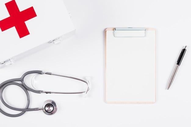 Trousse de premiers secours; stéthoscope et presse-papiers sur fond blanc Photo gratuit