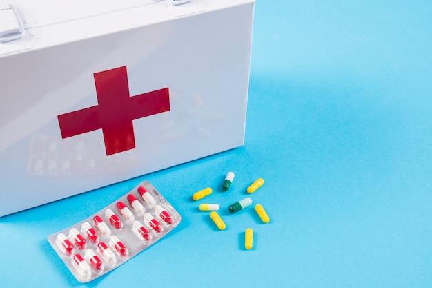 Trousse de secours blanche avec capsules colorées sur fond bleu Photo gratuit