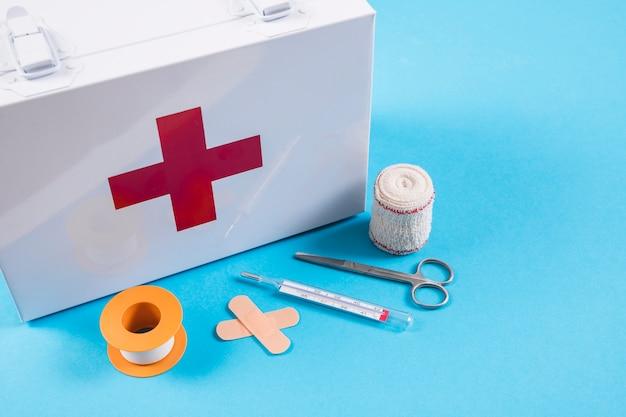 Trousse De Secours Blanche Avec Pansement Matériel Médical Sur Fond Bleu Photo Premium
