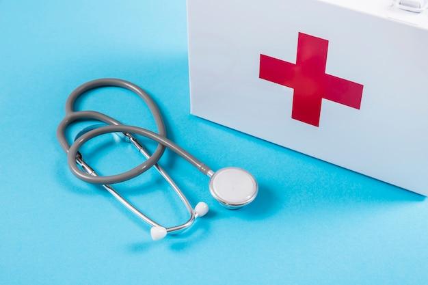 Trousse de secours blanche et stéthoscope sur fond bleu Photo gratuit