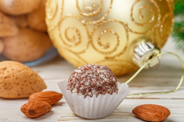Truffes au chocolat faites maison aux amandes sur une table en bois blanche avec des branches de sapin et des balles de jouets festifs Photo Premium