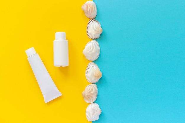 Tube blanc, bouteille de crème solaire et ligne de coquillages sur fond jaune et bleu, maquette Photo Premium