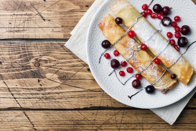 Tube de crêpes au chocolat et baies sur une assiette. fond en bois espace de copie Photo Premium