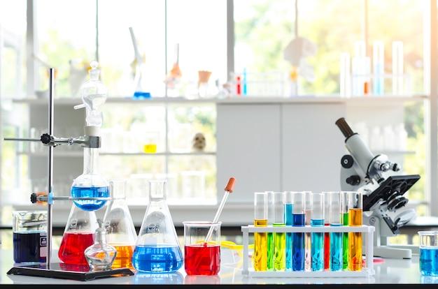 Tube à essai de liquide chimique et microscope en laboratoire. Photo Premium