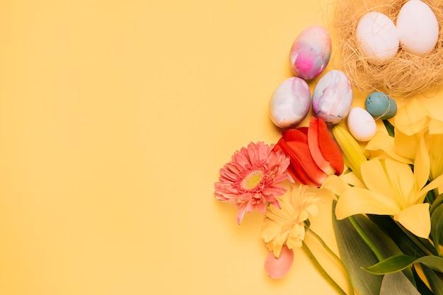 Tulipe; gerbera et fleurs de lys avec des oeufs de pâques sur fond jaune Photo gratuit
