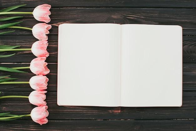 Tulipes avec cahier vierge sur la table Photo gratuit