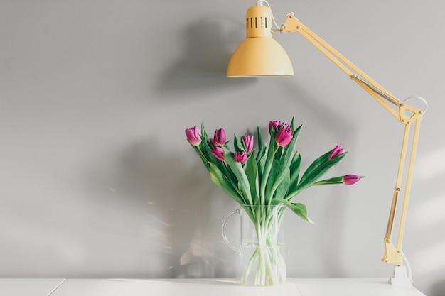 Tulipes Dans Un Vase Et Une Lampe Jaune à L'intérieur De La Maison Sur Un Mur Gris Photo Premium