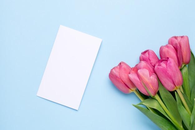 Tulipes de fleurs roses et carte présente sur une surface bleue Photo Premium