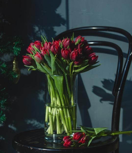 Tulipes fraîches rouges à l'intérieur d'un vase en verre avec de l'eau sur une chaise. Photo gratuit