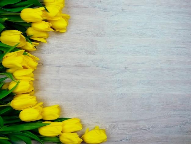 Tulipes jaunes sur l'espace de copie en bois. Photo Premium
