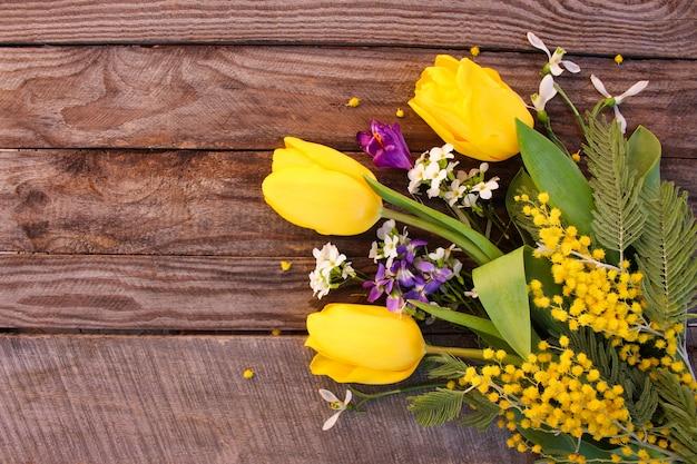 Tulipes jaunes, mimosa sur vieux bois Photo Premium