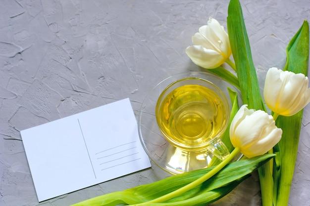 Tulipes de printemps tendres et une tasse de thé vert sur fond de ciment gris Photo Premium