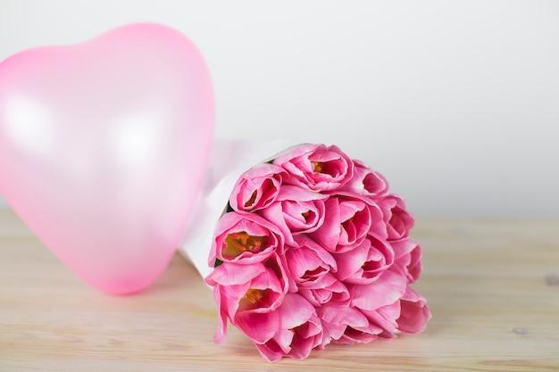 Tulipes roses et un ballon en forme de coeur. fond romantique Photo Premium
