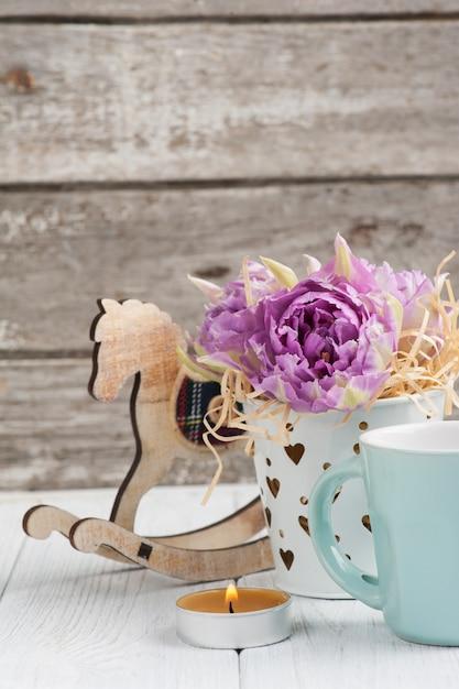 Tulipes roses, tasse bleue, bougie allumée et cheval à bascule Photo Premium