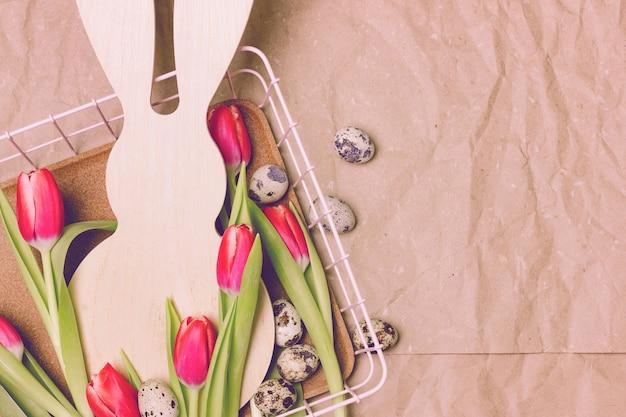 Tulipes roses tôt avec une forme de lapin sur un fond de papier beige. oeufs de caille traînent Photo Premium