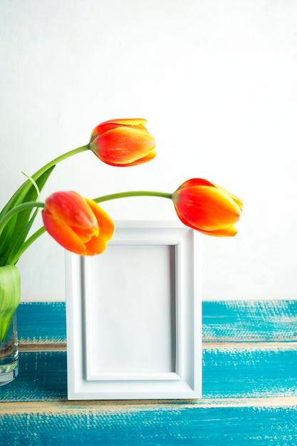 Tulipes rouges dans un vase en verre avec cadre vide Photo gratuit