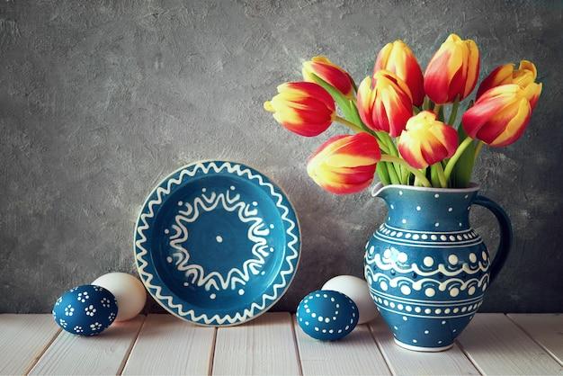 Tulipes rouges-jaunes dans un pichet en céramique bleue avec des oeufs de pâques et un tableau noir sur fond gris Photo Premium