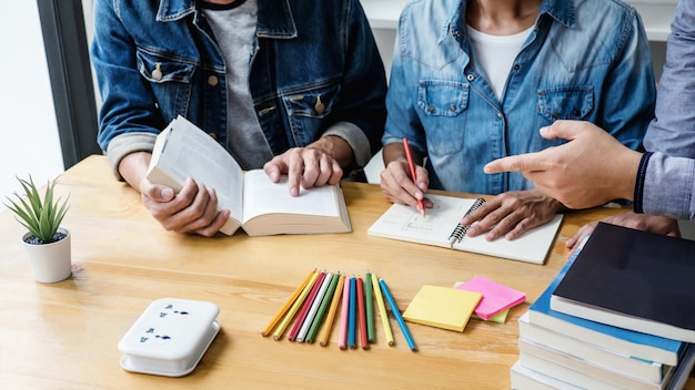 Tuteur d'école ou groupe d'étudiants collégiens assis à un bureau dans une bibliothèque étudiant et lisant, faisant ses devoirs et ses leçons se préparant à l'examen d'entrée, éducation, enseignement, concept d'apprentissage Photo Premium