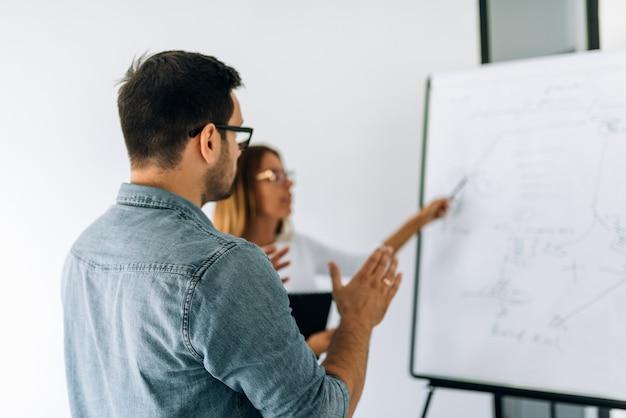 Un tuteur en train de donner un cours particulier à un jeune homme près du tableau dans le collège. Photo Premium