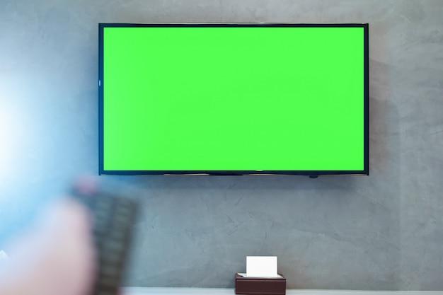 Tv à écran led avec écran vert au mur dans une chambre moderne avec télécommande floue Photo Premium