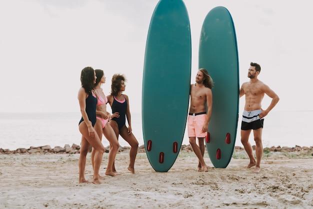 Two guys at beach détient des mecs. filles en maillot de bain. Photo Premium